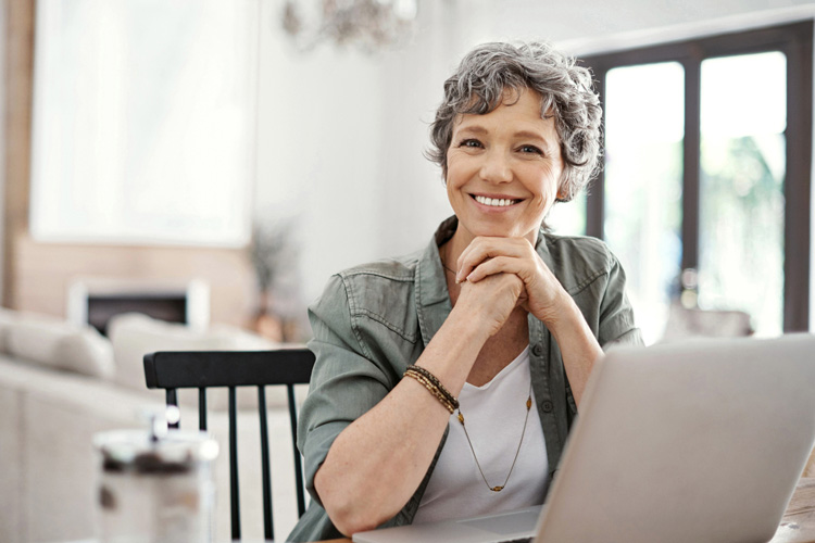 Woman looking up from laptop smiling