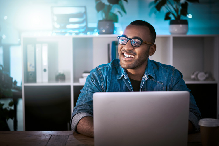 Man looking up from laptop smiling
