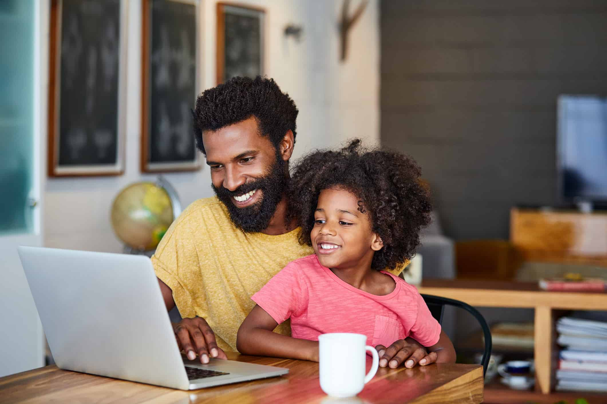 Father and daughter smiling at laptop
