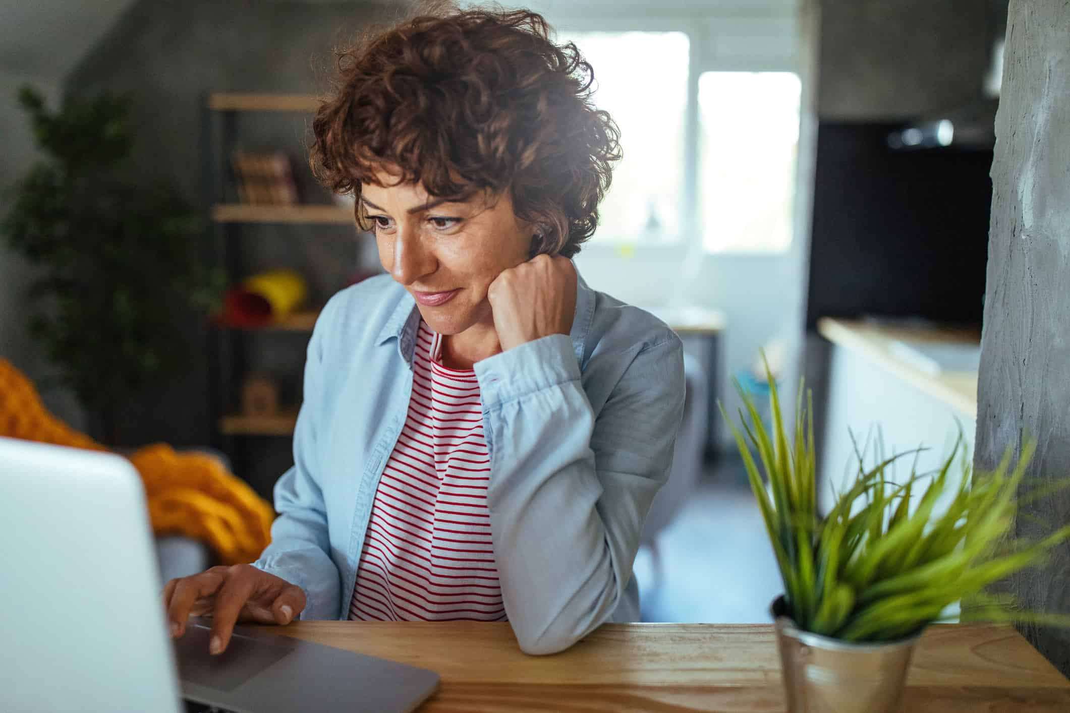 Woman using track-pad on laptop smiling